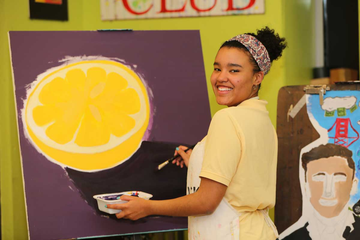 Student painting a lemon.