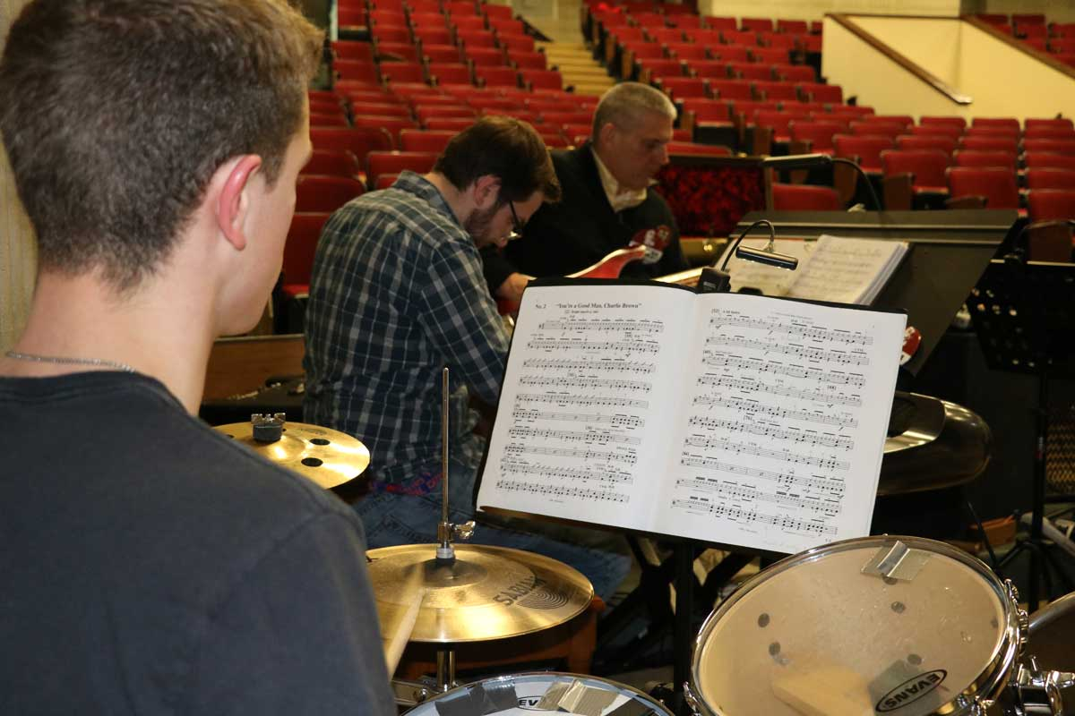 Drummer looks at usic in the orchestra pit for a Theatre Guild production.