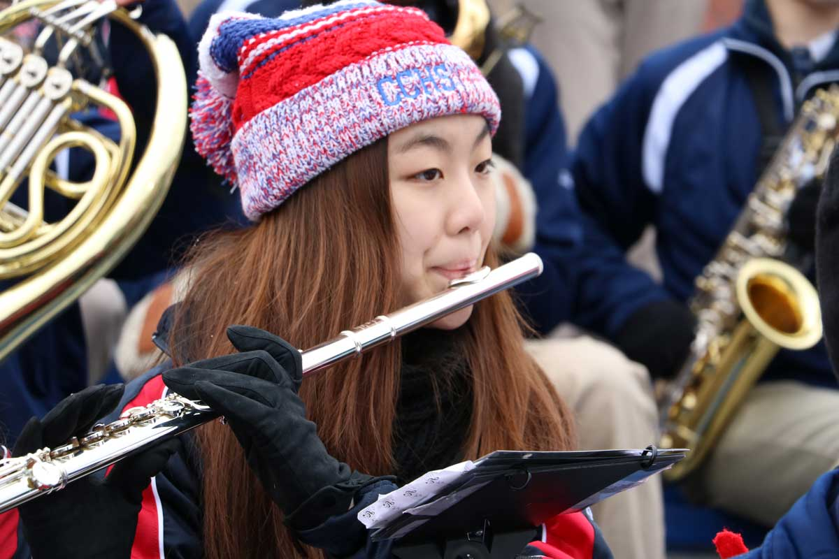Flute player performs in stands during a football game.