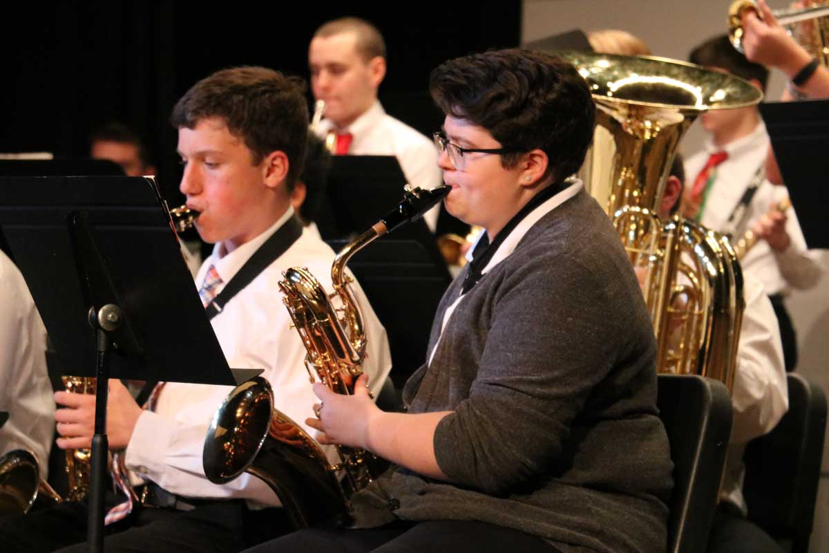 The saxophone section performs during a band concert.