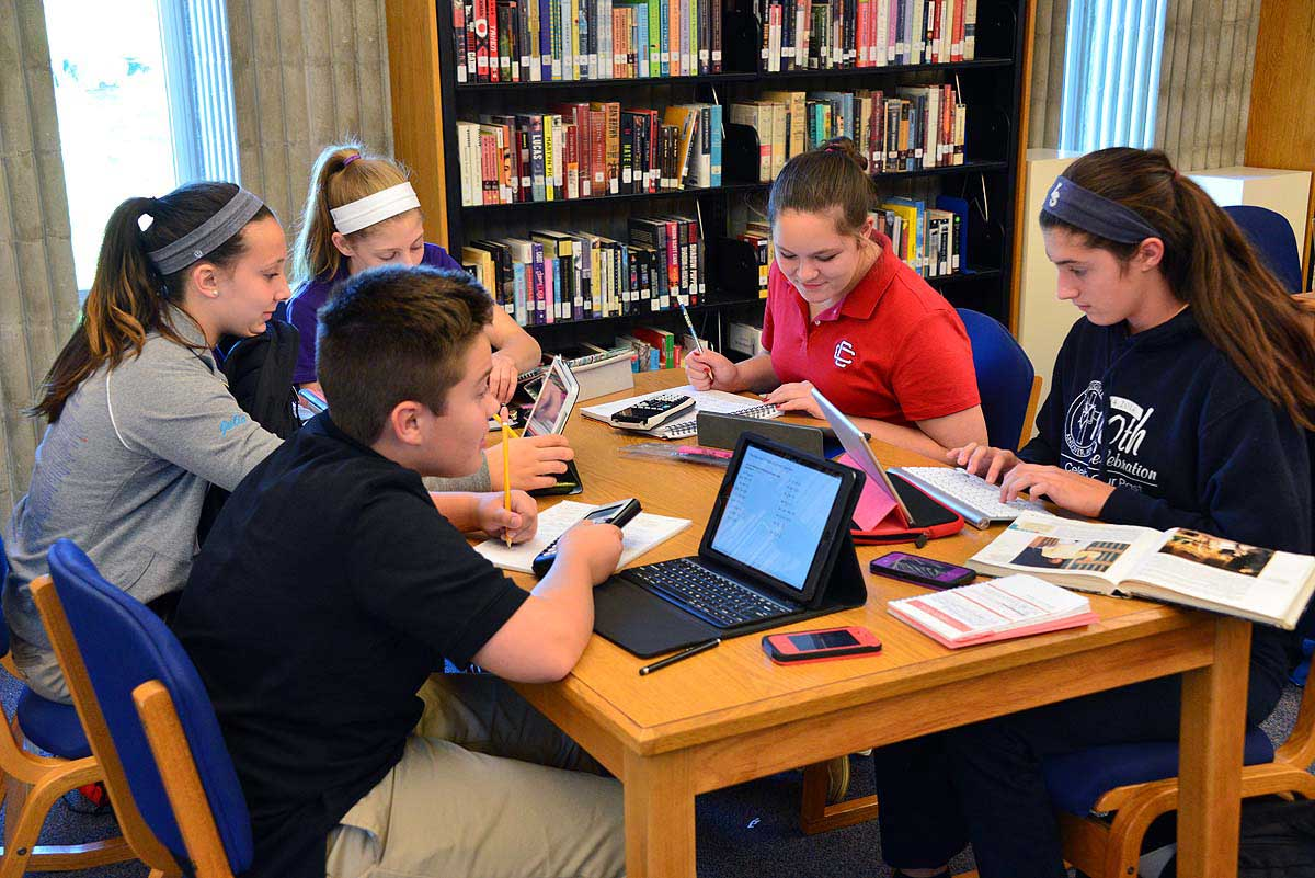Students work together at a table in the library.
