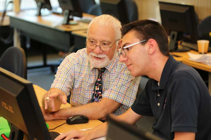 Mr. Staropoli wokrs with a student at a computer.